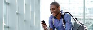 homem sorrindo e olhando o celular